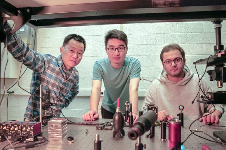 From left to right, Zongfu Yu, Ang Chen and Efram Khoram standing at a table in their lab