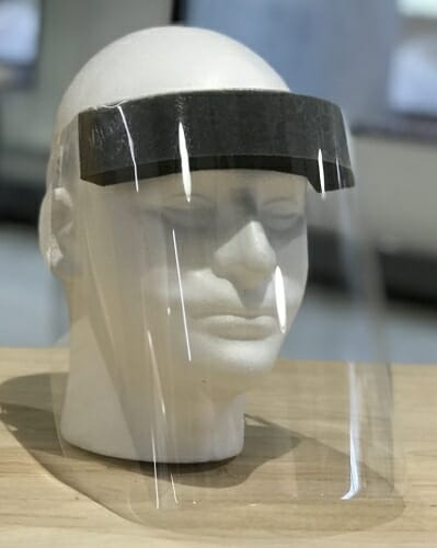 A clear plastic face shield on a dummy