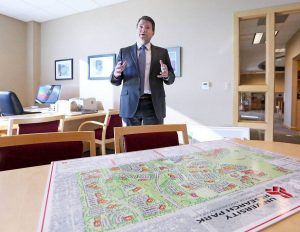 Aaron Olver stands at a table with a map of University Research Park on it.